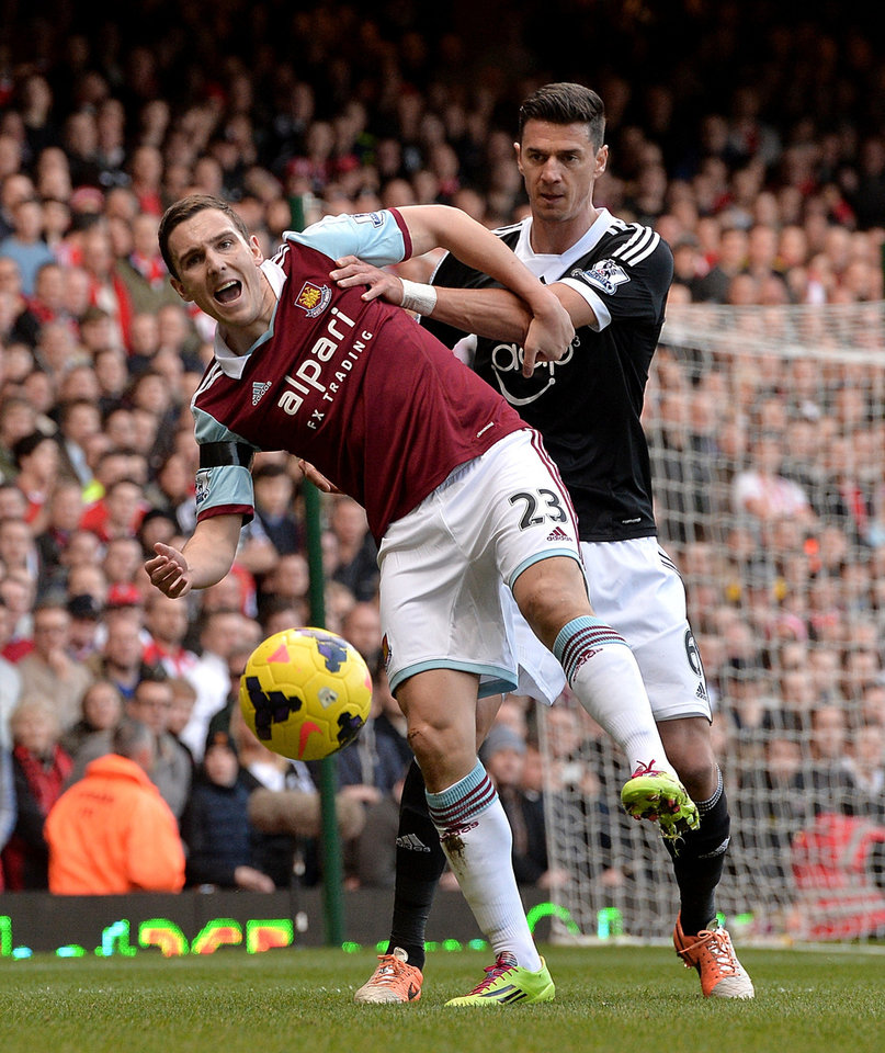 Photo - West Ham United's Stewart Downing (left) and Southampton's Jose Fonte battle for the ball during the English Premier League soccer match at Upton Park, London, Saturday, Feb. 22, 2014. (AP Photo / PA, Anthony Devlin) UNITED KINGDOM OUT
