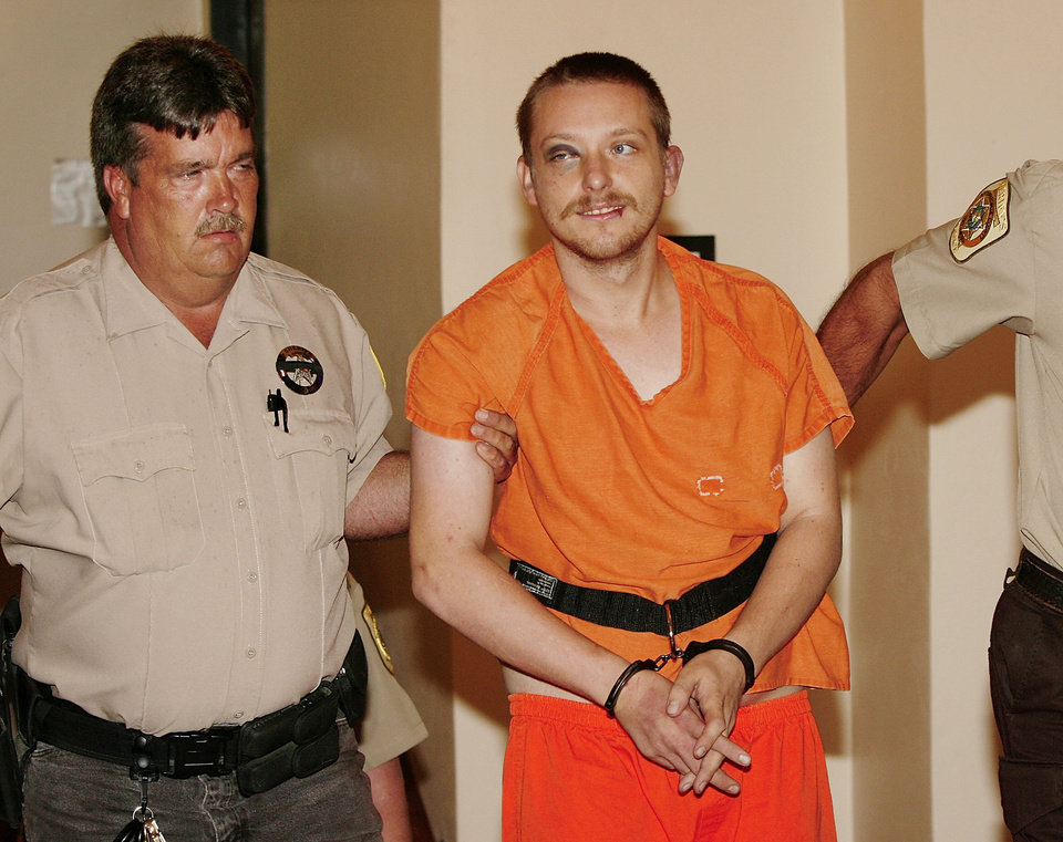 Photo - Ezekiel Holbert, 26, is led to a courtroom in the Seminole County Courthouse by Sheriff Shannon Smith, Monday, July 27, 2009. Holbert is suspect in shooting deaths of two of Smith's  deputies Sunday.  Photo by Jim Beckel, The Oklahoman