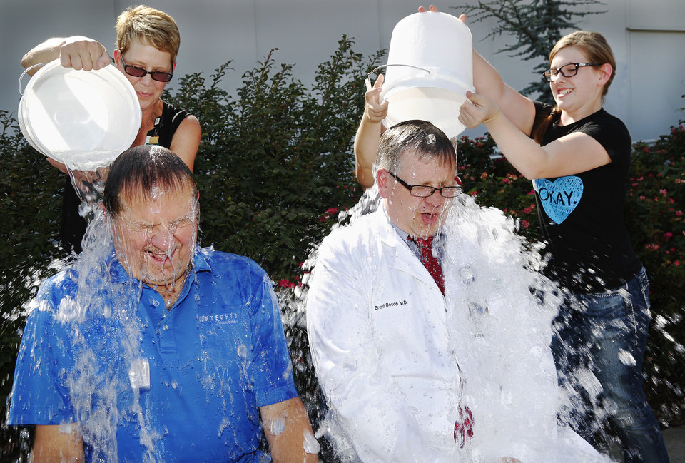 Photo - Bruce Lawrence, left, president and chief executive officer of INTEGRIS Health, was joined by Dr. Brent Beson, Medical Director of the INTEGRIS MDA Neuromuscular Center, were willing participants Tuesday afternoon, Aug. 19, 2014,  when they accepted the Ice Bucket Challenge in an effort to raise awareness of ALS services available  here in Oklahoma. The men had buckets of ice water poured on them in front of INTEGRIS Southwest Medical Center at SW 44 and Western Avenue. Pouring water on Lawrence's head is Julia Lyles, senior marketing representative for neurosciences.  Beson's children, Nicholas, 9, and Caitlin, 13, dumped ice water on their father's head. The Ice Bucket Challenge, sometimes referred to as the ALS Ice Bucket Challenge, is an activity involving dumping a bucket of ice water on a person's head to raise awareness and solicit donations for ALS treatment and research. It went viral throughout social media this summer. The challenge dares nominated participants to have a bucket of ice water poured on their head. One common stipulation gives 24 hours from the time they are nominated to complete the dare; otherwise, the participant is asked to donate money to charity. Photo by Jim Beckel, The Oklahoman