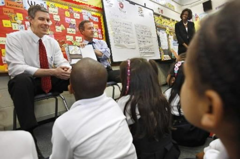 Photo - U.S. Secretary of Education  Arne  Duncan, left, and Maryland Gov. Martin O'Malley, read to first graders after a news conference about education stimulus funding, at Doswell Brooks Elementary School in Capitol Heights, Md. on Wednesday, April 1, 2009. (AP Photo/Jacquelyn Martin)