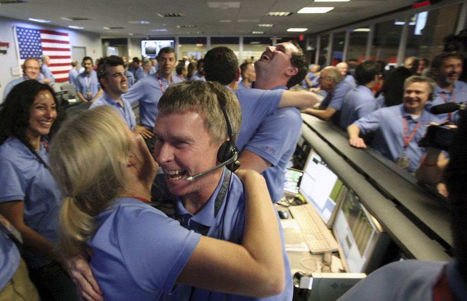Photo -   Telecom engineer Peter Llott, center, hugs a colleague to celebrate the successful landing of NASA's Mars Science Laboratory Curiosity rover inside the Spaceflight Operations Facilityat the Jet Propulsion Laboratory in Pasadena, Calif., Sunday, August 5, 2012. The Curiosity robot is equipped with a nuclear-powered lab capable of vaporizing rocks and ingesting soil, measuring habitability, and potentially paving the way for human exploration. (AP Photo/Brian van der Brug, Pool)