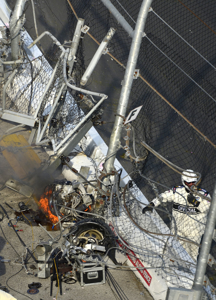The engine from Kyle Larson's car sits burning next to other parts from the car near a grandstand fence after the car hit the wall and safety fence along the front stretch on the final lap of the NASCAR Nationwide Series auto race at Daytona International Speedway in Daytona Beach, Fla., Saturday, Feb. 23, 2013. (AP Photo/Phelan M. Ebenhack)