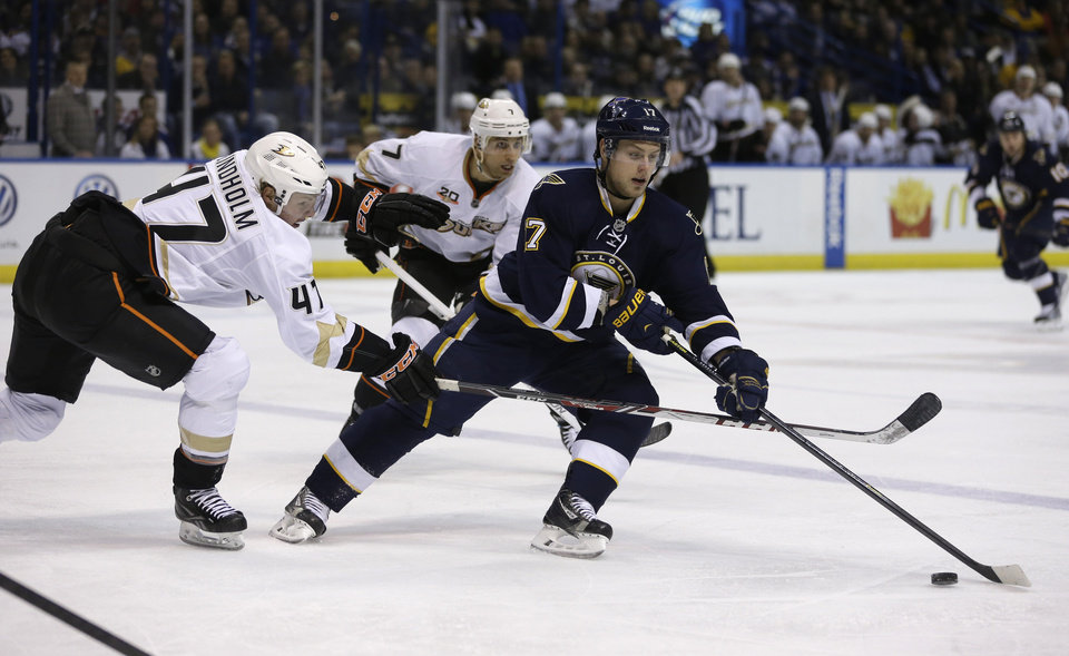 Photo - St. Louis Blues' Vladimir Sobotka, right, of the Czech Republic, controls the puck as Anaheim Ducks' Hampus Lindholm, left, of Sweden, and Andrew Cogliano, center, give chase during the second period of an NHL hockey game on Saturday, Jan. 18, 2014, in St. Louis. (AP Photo/Jeff Roberson)