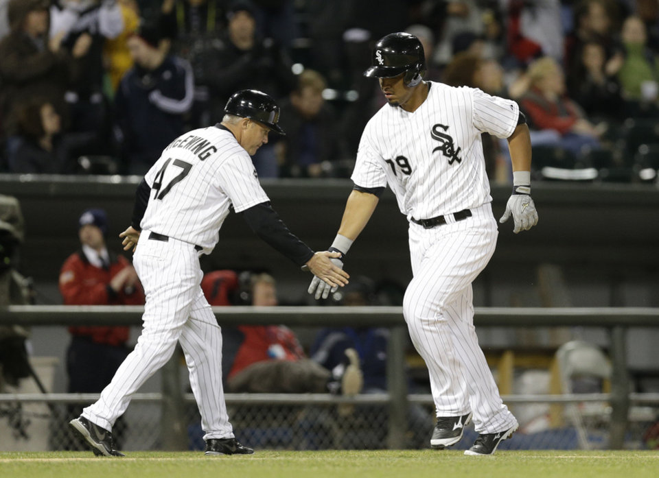 Photo - Chicago White Sox's Jose Abreu, right, celebrates with third base coach Joe McEwing after hitting a solo home run during the fifth inning of a baseball game against the Cleveland Indians in Chicago, Thursday, April 10, 2014. (AP Photo/Nam Y. Huh)