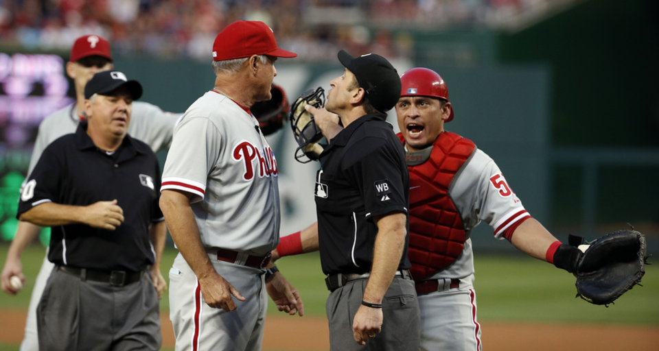 Photo - Home plate umpire Chris Guccione, second from right, talks with Philadelphia Phillies manager Ryne Sandberg, center, as catcher Carlos Ruiz tries to make a point, during the second inning of a baseball game against the Washington Nationals at Nationals Park Saturday, Aug. 2, 2014, in Washington. Both starting pitcher A.J. Burnett and Sandberg were ejected by Guccione. (AP Photo/Alex Brandon)
