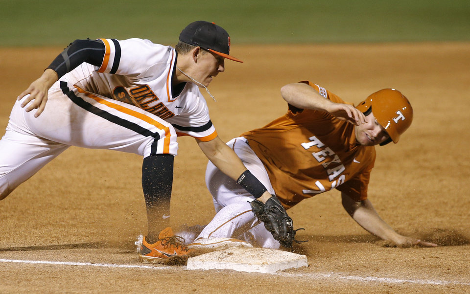 Photo - OSU's Craig McConaughy tags out Texas' Weston Hall at third in the ninth inning of a Big 12 Tournament baseball game between Oklahoma State University and the University of Texas at Chickasaw Bricktown Ballpark in Oklahoma City, Saturday, May 24, 2014. Photo by Bryan Terry The Oklahoman