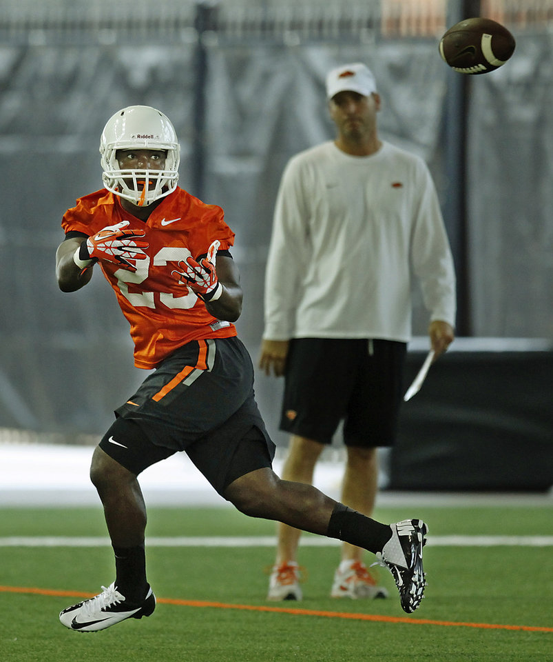 Photo - Oklahoma State running back Rennie Childs (23) catches the ball during the first team practice of the fall at the Sherman E. Smith Training Facility on the campus of Oklahoma State University in Stillwater on August 1, 2014. Photo by KT King, The Oklahoman