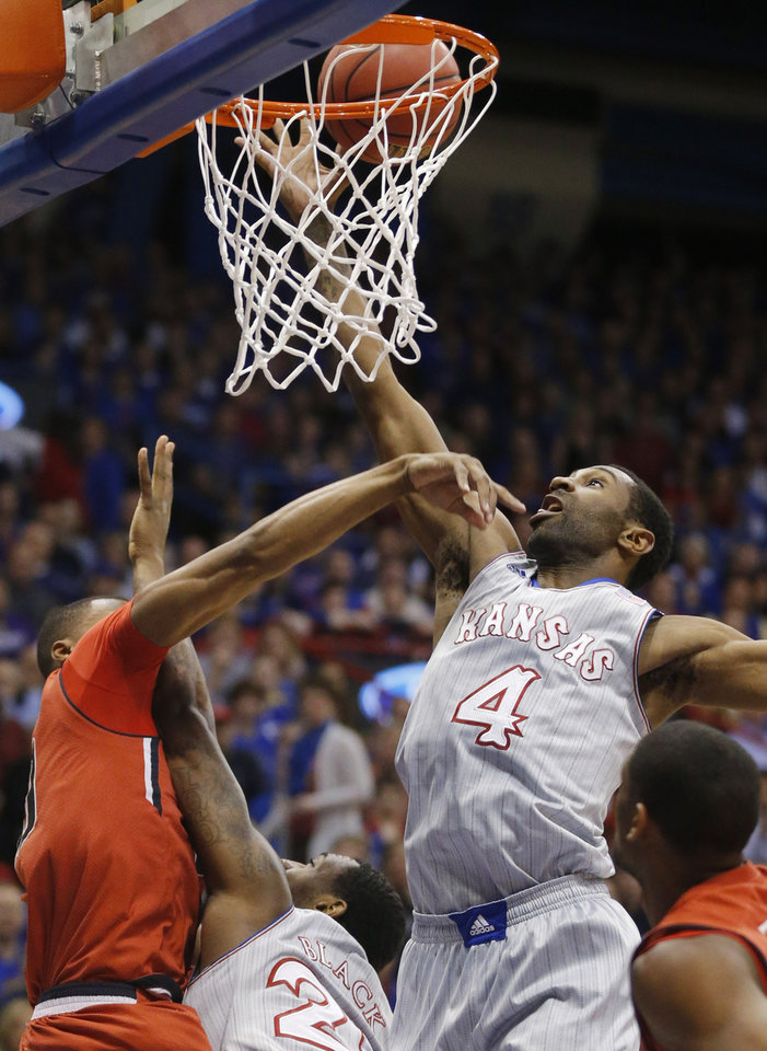 Photo - Kansas forward Justin Wesley (4) reaches for a rebound during the first half of an NCAA college basketball game against Texas Tech in Lawrence, Kan., Wednesday, March 5, 2014. (AP Photo/Orlin Wagner)