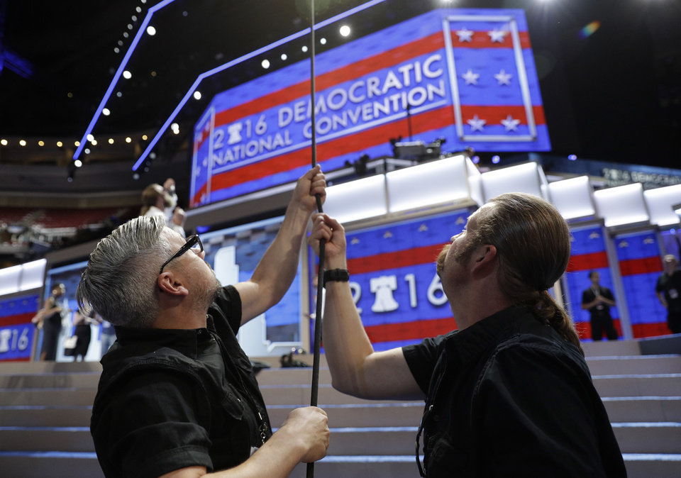 Photo - Travis Salomone, left, and Mike Atkinson, hoist a light into place during preparations before the start of the 2016 Democratic Convention, Monday, July 25, 2016, in Philadelphia. (AP Photo/John Locher)