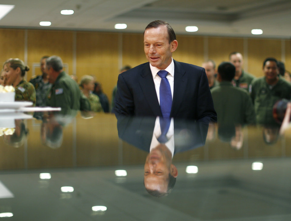 Photo - Australian Prime Minister Tony Abbott is reflected in glass as he serves himself breakfast at a buffet during his visit to RAAF Base Pearce, where various international forces are currently based as they search for the missing Malaysia Airlines Flight 370, in Bullsbrook, near Perth, Australia, on Monday March 31, 2014. (AP Photo/Jason Reed, Pool)