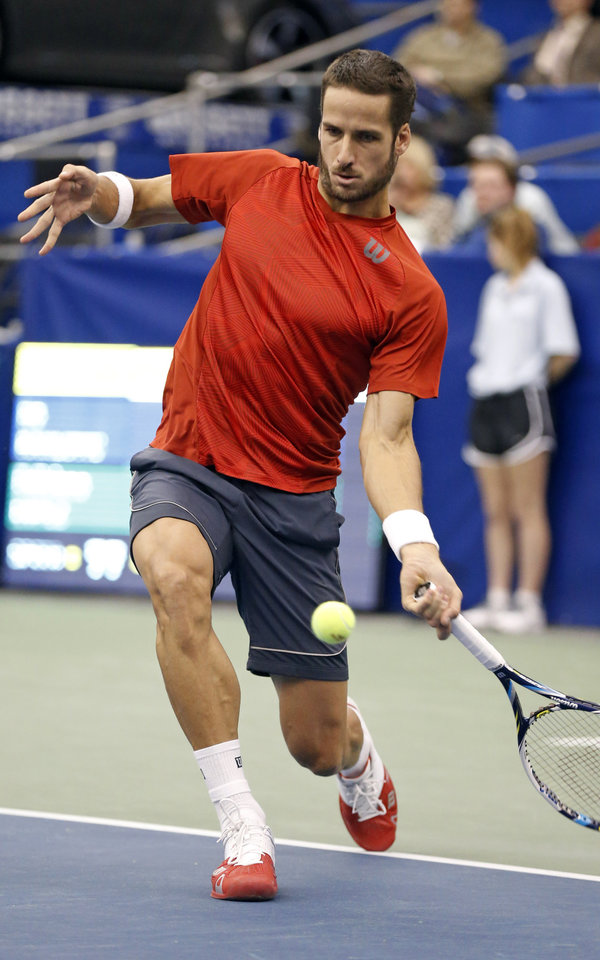 Photo - Spain's Feliciano Lopez, of Spain, reaches low for a return to Ivo Karlovic, of Croatia, during aU.S. National Indoor Tennis Championships match Thursday, Feb. 13, 2014, in Memphis, Tenn. (AP Photo/Rogelio V. Solis)