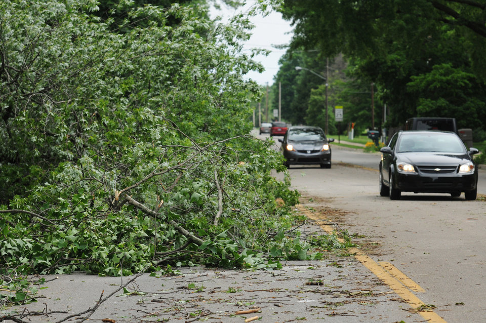 Photo - Cars drive by damaged tree limbs after a storm in St. Joseph Township, Mich., Tuesday, July 1, 2014. Severe thunderstorms packing high winds knocked down trees and power lines across parts of Michigan, leaving more than 230,000 without power and injuring a firefighter. (AP Photo/The Herald-Palladium, Don Campbell)