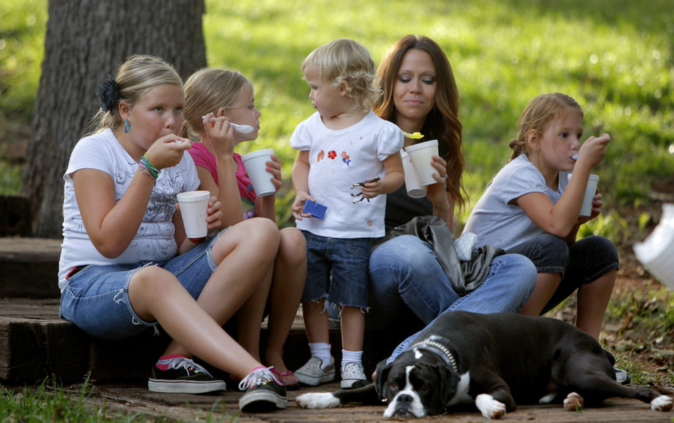 Photo - From left, Taylor Armstrong, 10, Rylee Armstrong, 2, Kamryn Armstrong 2, mother Lindsey Armstrong, and Morgan Armstrong, 6, eat snow cones Thursday during the 2012 Edmond Summer Concert Series at E.C. Hafer Park.  BRYAN TERRY - THE OKLAHOMAN