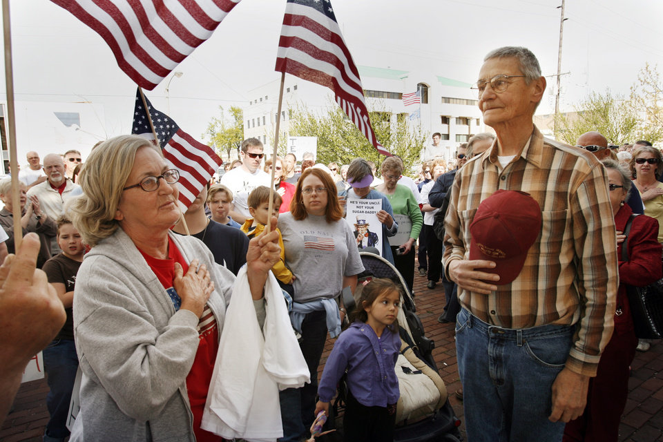 Photo - Senith Hickey of Dibble, and Larry Iovan of Slaughterville join the flag salute as citizens hold a Tax Day Tea Party at the Santa Fe Station in Norman, Okla. on Wednesday, April 15, 2009.  
