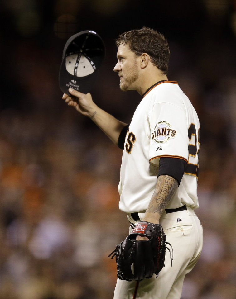 Photo - San Francisco Giants' Jake Peavy removes his cap for fans during a standing ovation after leaving the baseball game against the Milwaukee Brewers in the eighth inning Saturday, Aug. 30, 2014, in San Francisco. (AP Photo/Ben Margot)