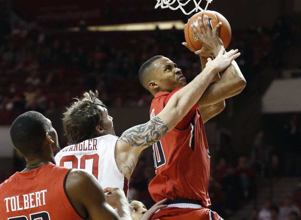 Photo - Texas Tech forward Jaye Crockett (30) is fouled by Oklahoma forward Ryan Spangler (00) as he shoots during the first half on an NCAA college basketball game in Norman, Okla., Wednesday, Feb. 12, 2014. (AP Photo/Sue Ogrocki)