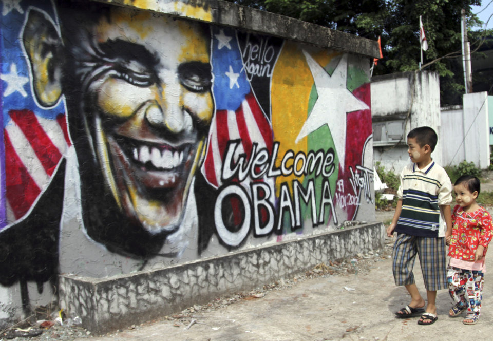 Photo -   Myanmar children walk near a graffiti painted by Myanmar artist Arker Kyaw to welcome U.S. President Barack Obama on a street in Yangon, Myanmar, Saturday, Nov. 17, 2012. Word of Obama's historic visit has spread quickly around Yangon, which is readying itself with legions of hunched workers painting fences and curbs, pulling weeds and scraping grime off old buildings in anticipation of the president's Monday arrival. (AP Photo/Khin Maung Win)