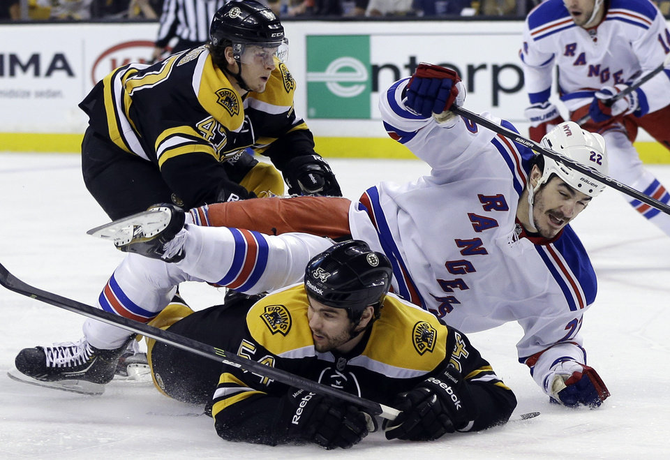 Photo - New York Rangers center Brian Boyle (22) goes down to the ice as he chases the puck against Boston Bruins defensemen Adam McQuaid (54) and Torey Krug (47) during the first period in Game 2 of the NHL Eastern Conference semifinal hockey playoff series in Boston, Sunday, May 19, 2013. (AP Photo/Elise Amendola)