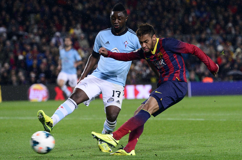 Photo - FC Barcelona's  Neymar, from Brazil, scores against Celta Vigo's Levy Madinda during a Spanish La Liga soccer match at the Camp Nou stadium in Barcelona, Spain, Wednesday, March 26, 2014. (AP Photo/Manu Fernandez)
