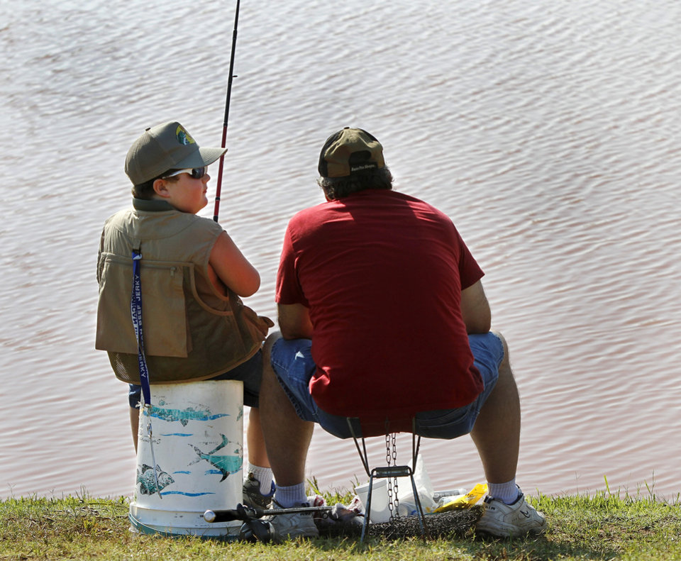 Photo - Chris Wiems and his son, Colton, 6, of Moore, sit together while fishing at the derby.  Moore hosted its annual kids fishing derby Saturday morning, July 27, 2013,  at Buck Thomas Park.  As part of the event this year, a charity called the Tackle the Storm Foundation handed out rods and reels to tornado victims. Several bass fishing pros from Oklahoma attended the event to help distribute the fishing equipment and share fishing tips with the young anglers. An event official  said about 250 children participated in the fishing derby. Photo  by Jim Beckel, The Oklahoman.