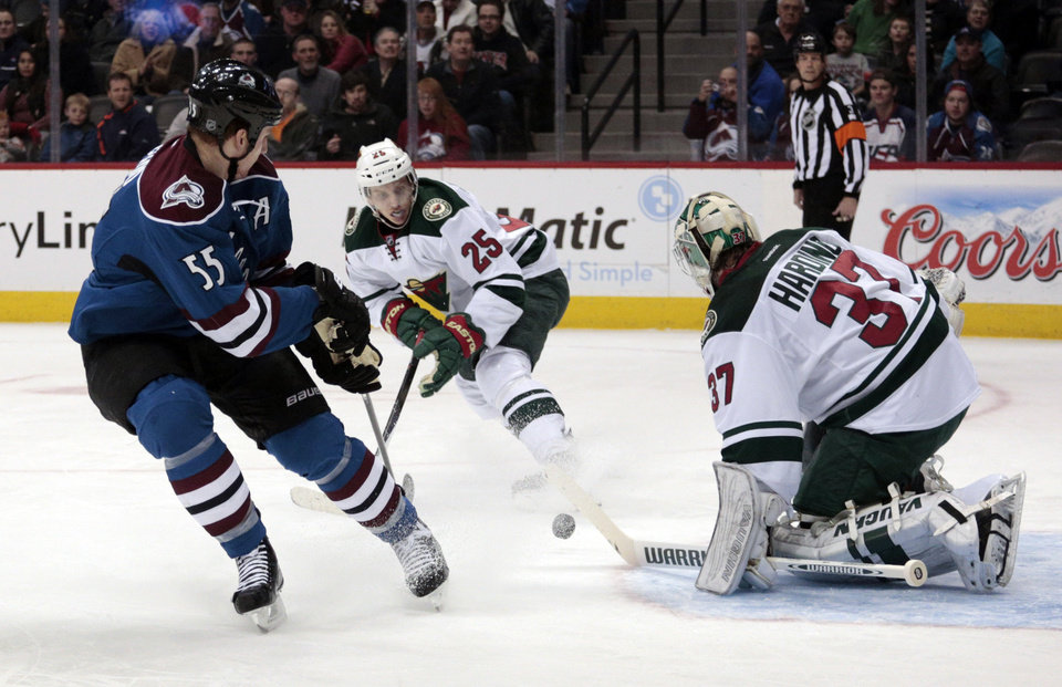 Photo - Minnesota Wild goalie Josh Harding (37) stops a shot by Colorado Avalanche left wing Cody McLeod (55) as Wild defenseman Jonas Brodin (25) defends during the first period of an NHL hockey game in Denver on Saturday, Dec. 14, 2013. (AP Photo/Joe Mahoney)
