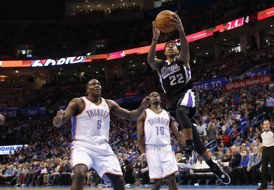 Photo - Sacramento Kings guard Isaiah Thomas (22) shoots in front of Oklahoma City Thunder center Kendrick Perkins (5) and guard Reggie Jackson (15) in the first quarter of an NBA basketball game in Oklahoma City, Sunday, Jan. 19, 2014. (AP Photo/Sue Ogrocki)
