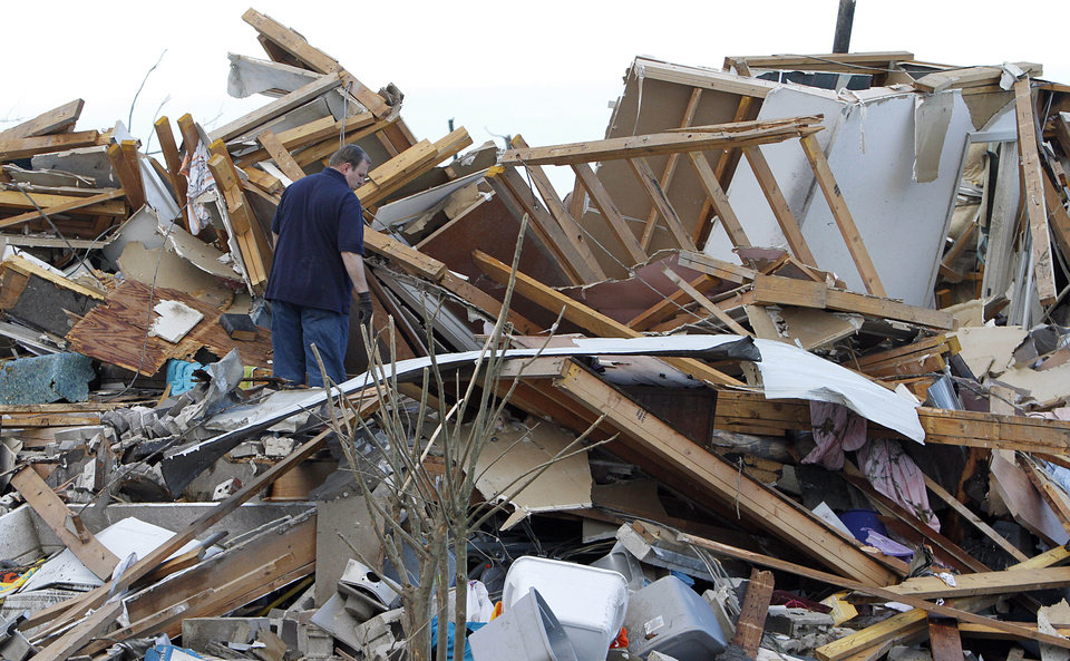 Photo - A resident searches through what is left of his home after a tornado hit a day earlier in Pleasant Grove, just west of downtown Birmingham, Ala., on Thursday, April 28, 2011. (AP Photo/Butch Dill)