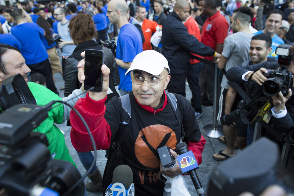 Photo -   Hazem Sayed, 54, the first in line to purchase the new iPhone 5, holds up his new phone in front of media outside the Fifth Avenue Apple store, Friday, Sept. 21, 2012, in New York. Hundreds of people waited in line through the early morning to be among the first to get their hands on the highly anticipated phone. (AP Photo/John Minchillo)