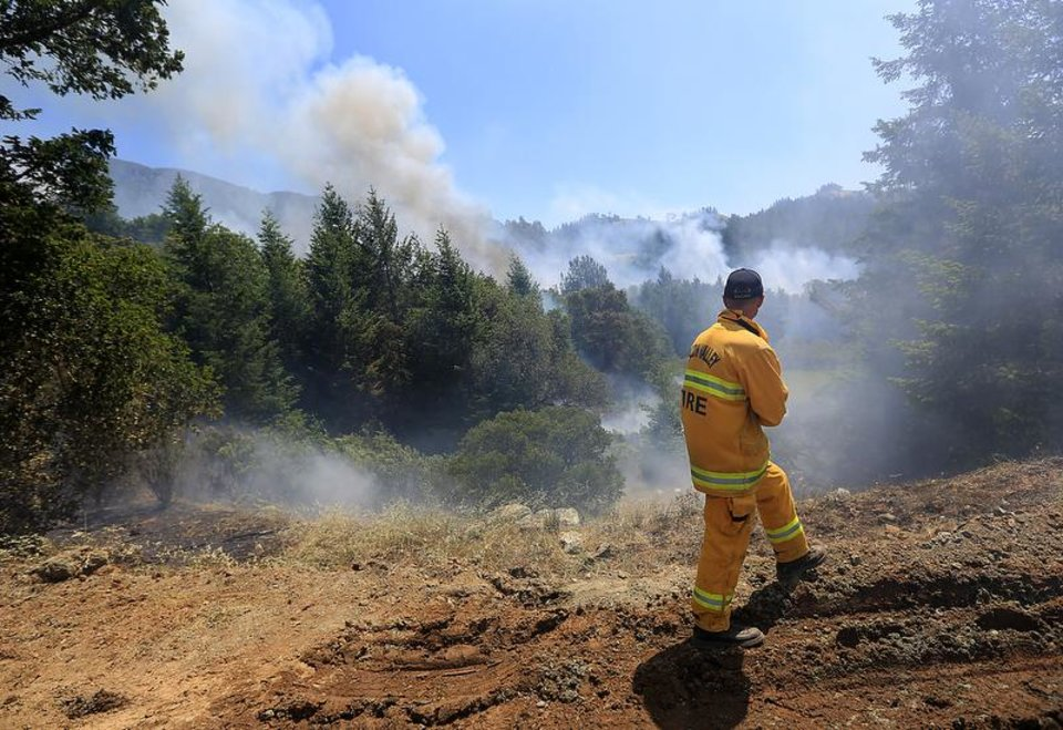 Rincon Valley firefighter Nate DeJung keeps check on the head of the Yellow fire above Knights Valley, Calif., Wednesday May 1, 2013. The fire started early Wednesday morning on the rugged border between Napa and Sonoma Counties and roared through tall stands of pine trees. Crews were securing the perimeter of the fire in the afternoon. (AP Photo/Santa Rosa Press Democrat, Kent Porter)