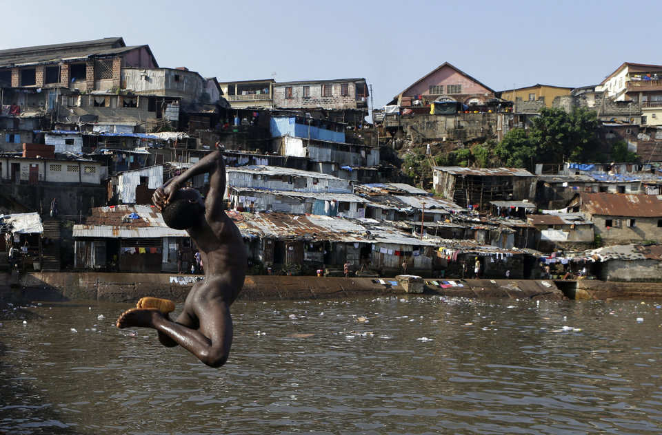 A boy leaps into the water off a pier in the Mabella slum of Freetown, Sierra Leone Friday, Nov. 16, 2012. Ten years after the end of a devastating civil war, Sierra Leone will go to the polls on Saturday to choose between incumbent President Ernest Bai Koroma and opposition leader Julius Maada Bio. (AP Photo/Rebecca Blackwell)
