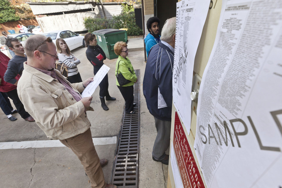 Brian Westbrook, left, looks over a ballot outside of a poLling place in Little Rock, Ark., Tuesday, Nov. 6, 2012. (AP Photo/Danny Johnston)