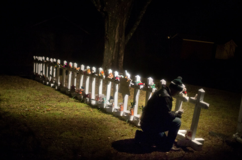 Photo - Frank Kulick, adjusts a display of wooden crosses, and a Jewish Star of David, representing the victims of the Sandy Hook Elementary School shooting, on his front lawn, Monday, Dec. 17, 2012, in Newtown, Conn. (AP Photo/David Goldman)