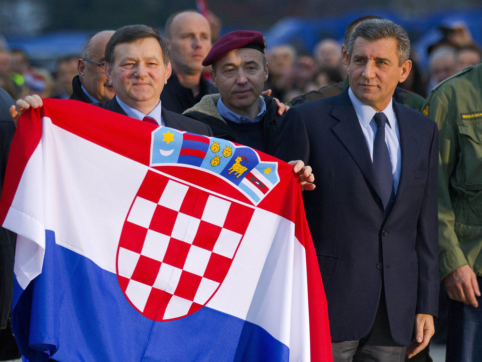 Photo -   Croatian Gen. Ante Gotovina, right and Gen. Mladen Markac hold the Croatian flag upon their arrival to the airport in Zagreb, Croatia, Friday, Nov. 16, 2012. The Yugoslav war crimes tribunal overturned the convictions of the two Croat generals on Friday for murdering and illegally expelling Serb civilians in a 1995 military blitz, and ordered both men to be freed immediately. (AP Photo/Nikola Solic)