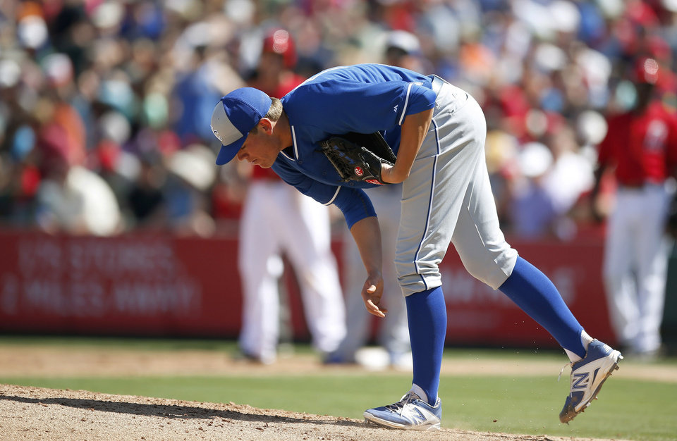 Photo - Kansas City Royals' Aaron Brooks leans over to take a swipe at the pitcher's mound after giving up a run to the Los Angeles Angels during the second inning of a spring training baseball game on Friday, March 21, 2014, in Tempe, Ariz. (AP Photo/Ross D. Franklin)