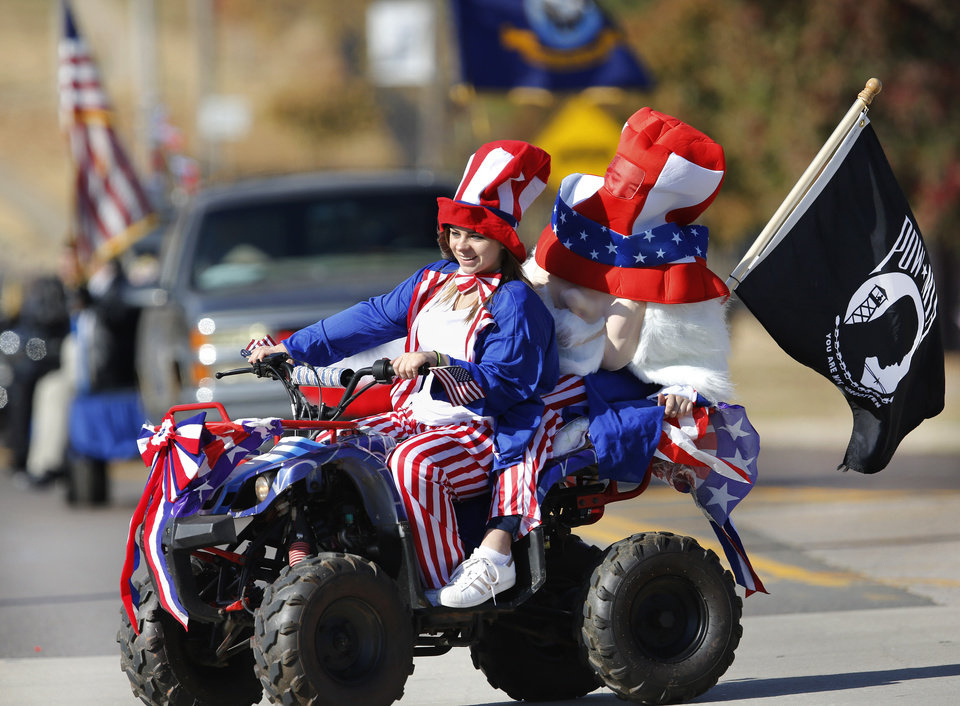 Photo - Two people dressed in patriotic costumes ride a four-wheeler in the Midwest City Veteran's Day Parade on Friday, Nov. 10, 2017. Photo by Jim Beckel, The Oklahoman