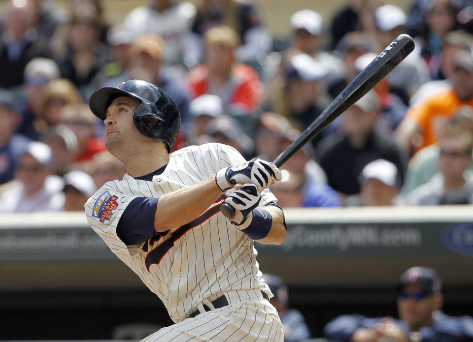 Photo - Minnesota Twins' Brian Dozier watches the flight of his solo home run off Baltimore Orioles starting pitcher Wei-Yin Chen during the third inning of a baseball game in Minneapolis, Saturday, May 3, 2014. (AP Photo/Ann Heisenfelt)