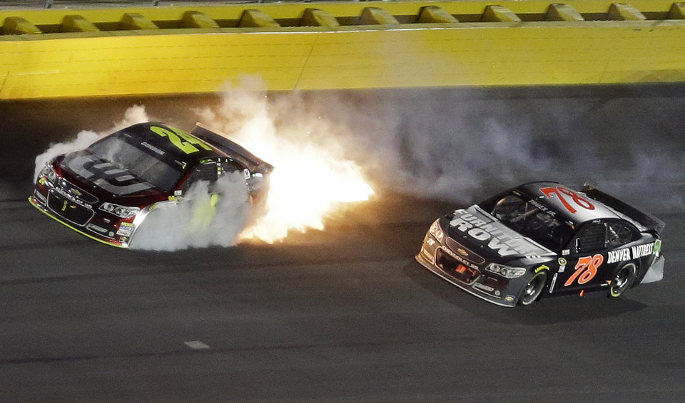 Photo - Smoke and flames come from Jeff Gordon's car after a collision with Martin Truex Jr. (78) during the NASCAR Sprint All-Star auto race at Charlotte Motor Speedway in Concord, N.C., Saturday, May 17, 2014. (AP Photo/Gerry Broome)
