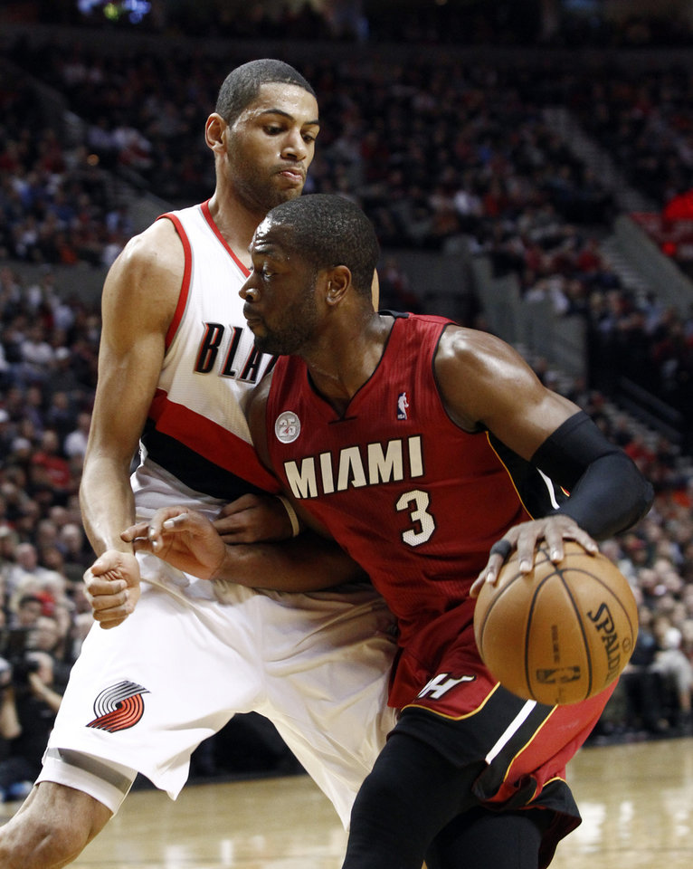 Photo - Miami Heat guard Dwayne Wade, right, drives on Portland Trail Blazers forward Nicolas Batum, from France, during the first quarter of an NBA basketball game in Portland, Ore., Thursday, Jan. 10, 2013. (AP Photo/Don Ryan)