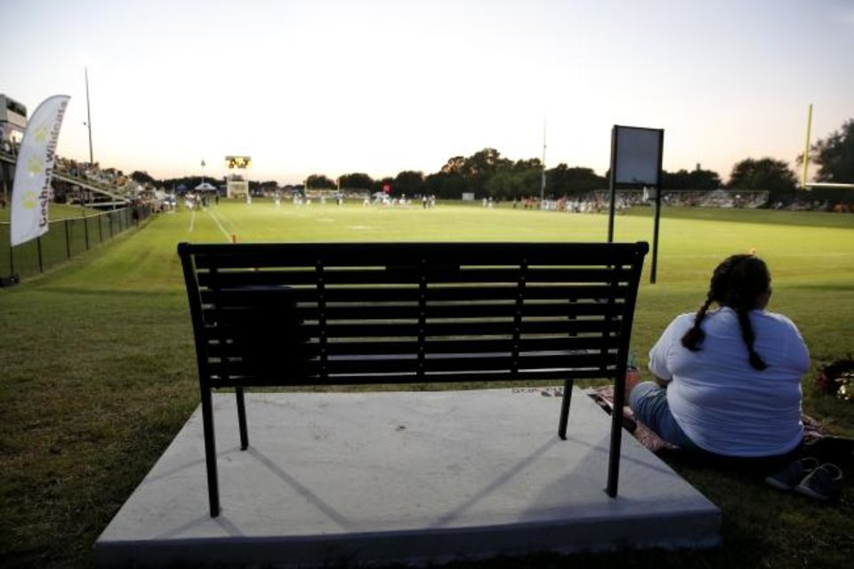 Photo -  A bench dedicated to Jacie Cochran sits on the hill behind the east end one at Cashion High School. [Bryan Terry/The Oklahoman]