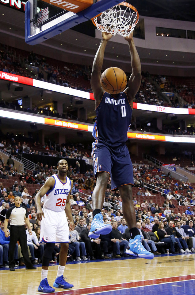 Photo - Charlotte Bobcats' Bismack Biyombo (0) dunks the ball past Philadelphia 76ers' Elliot Williams during the first half of an NBA basketball game, Wednesday, April 2, 2014, in Philadelphia. (AP Photo/Matt Slocum)