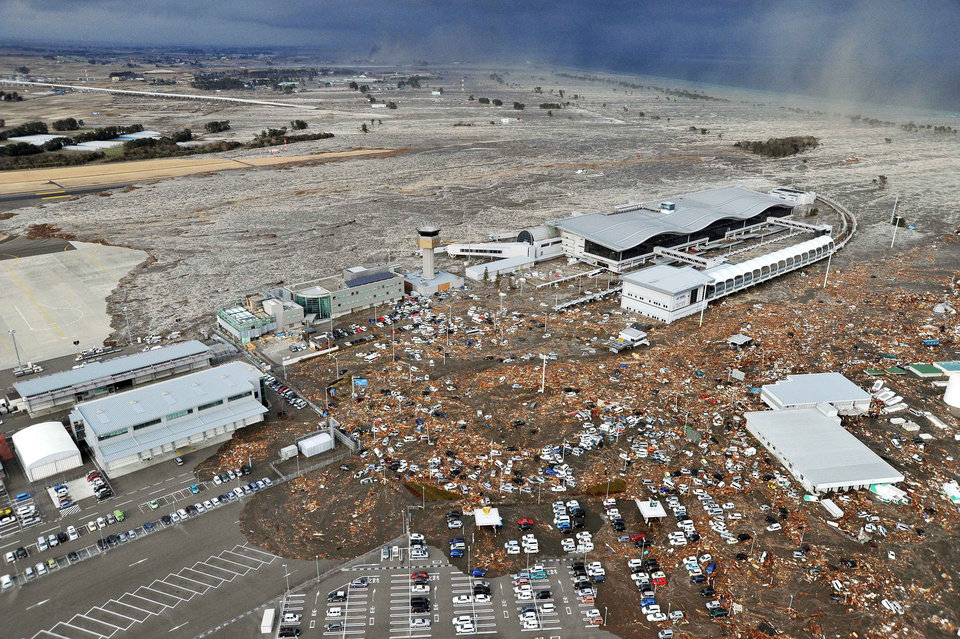 Photo - Tarmac, parking lot and surrounding area are covered with mud and debris carried by tsunami at Sendai Airport in Sendai, Miyagi Prefecture (state) after Japan was struck by a strong earthquake off its northeastern coast Friday, March 11, 2011. (AP Photo/Kyodo News) JAPAN OUT, MANDATORY CREDIT, FOR COMMERCIAL USE ONLY IN NORTH AMERICA ORG XMIT: TOK824
