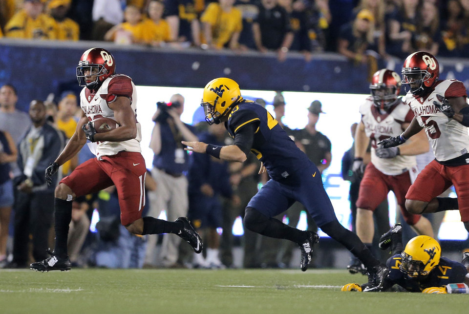 Photo - Oklahoma's Alex Ross (28) returns a kick off as West Virginia's Hunter Brown chases him down during the college football game between West Virginia  Mountaineers and the University of Oklahoma Sooners at Milan Puskar Stadium in Morgantown, W.Va., Saturday, Sept. 20, 2014. Photo by Sarah Phipps, The Oklahoman