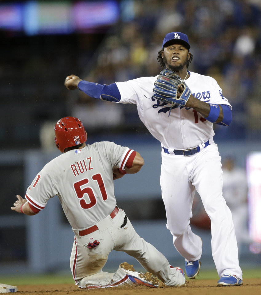 Photo - Los Angeles Dodgers shortstop Hanley Ramirez, right, throws to first base to complete a double play after forcing out Philadelphia Phillies' Carlos Ruiz during the seventh inning of a baseball game on Thursday, April 24, 2014, in Los Angeles. Philadelphia Phillies' Ryan Howard was out at first. (AP Photo/Jae C. Hong)