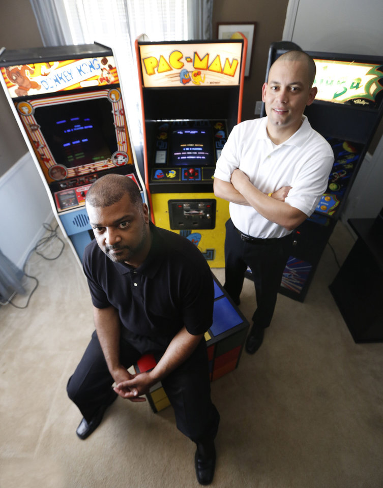 Photo - Mark Temple, left,  and Jose Rodriguez pose with 1980s video games Wednesday in Oklahoma City. Rodriguez and Temple are opening an '80s themed bar on NW 23. Photo By Steve Gooch, The Oklahoman  Steve Gooch