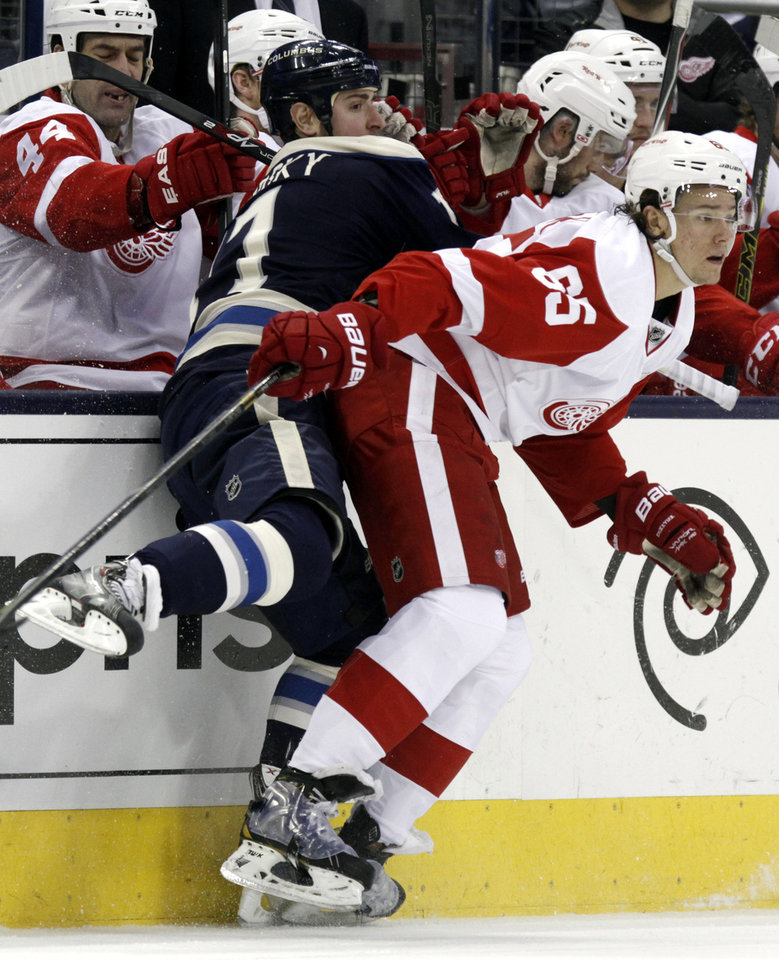Photo - Detroit Red Wings' Danny DeKeyser, right, checks Columbus Blue Jackets' Brandon Dubinsky in the first period of an NHL hockey game in Columbus, Ohio, Tuesday, March 25, 2014. (AP Photo/Paul Vernon)