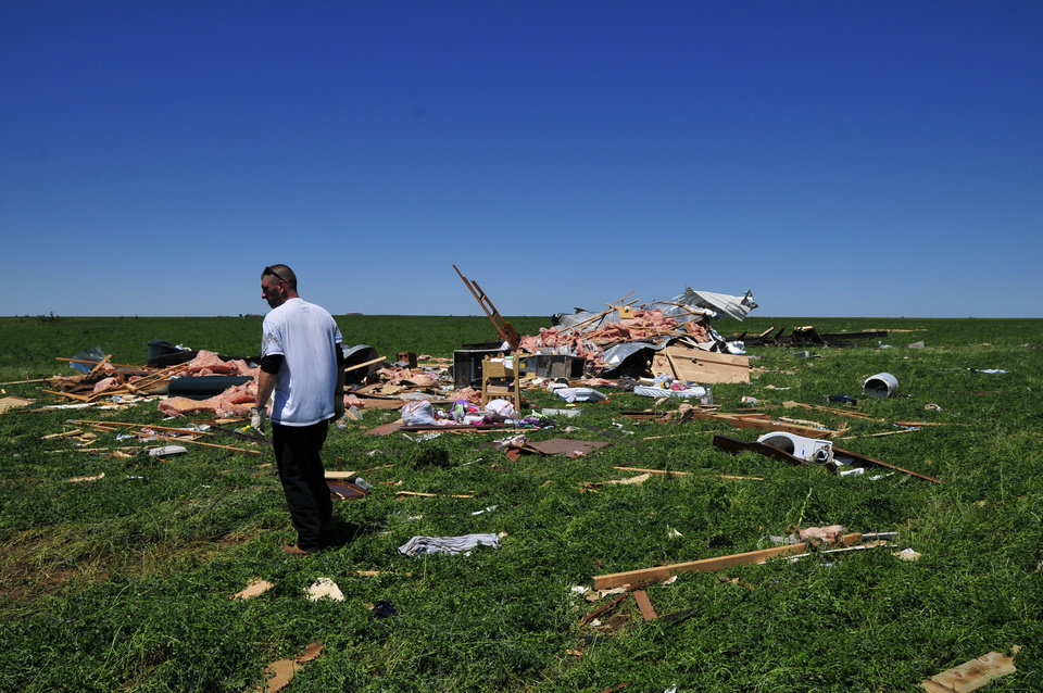 Photo - Joshua Lamb stands near what was once he and his family's home that was left in ruins by a tornado, Saturday June 1, 2013 in El Reno Okla. (AP Photo/Nick Oxford)