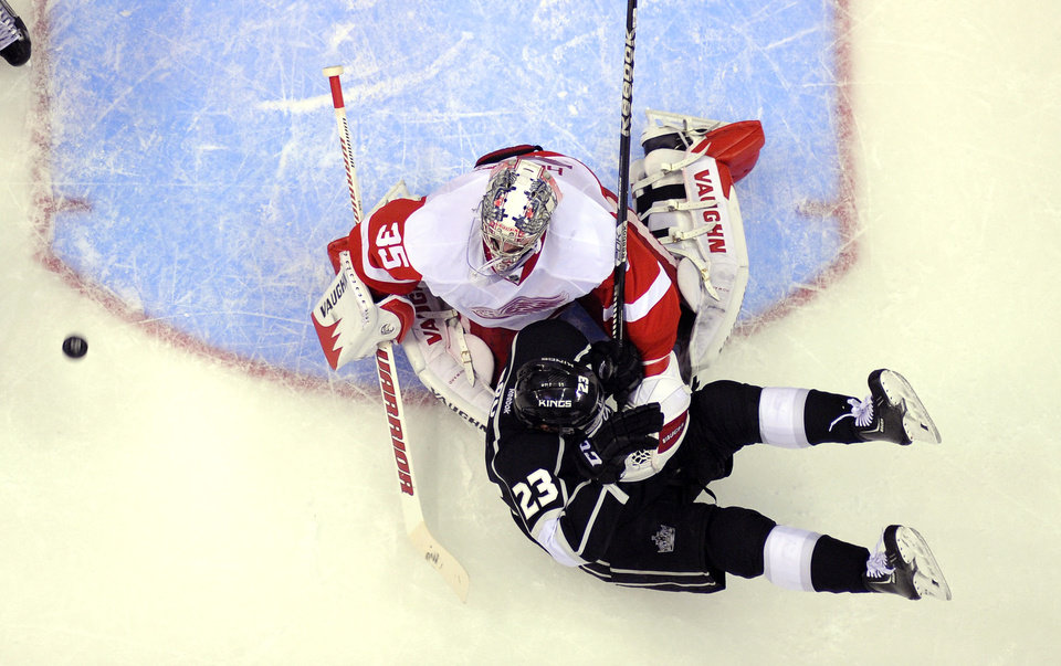 Photo - Detroit Red Wings goalie Jimmy Howard, top, is scored on by Los Angeles Kings defenseman Drew Doughty, not seen, as right wing Dustin Brown takes a fall during the first period of an NHL hockey game, Saturday, Jan. 11, 2014, in Los Angeles. (AP Photo/Mark J. Terrill)