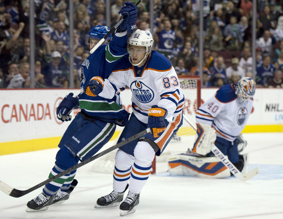 Photo - Vancouver Canucks center Brad Richardson (15) celebrates his first-period goal against Edmonton Oilers goalie Devan Dubnyk (40) as Oilers right wing Ales Hemsky (83) skates by during an NHL hockey game in Vancouver, British Columbia, Saturday, Oct. 5, 2013. (AP Photo/The Canadian Press, Jonathan Hayward)