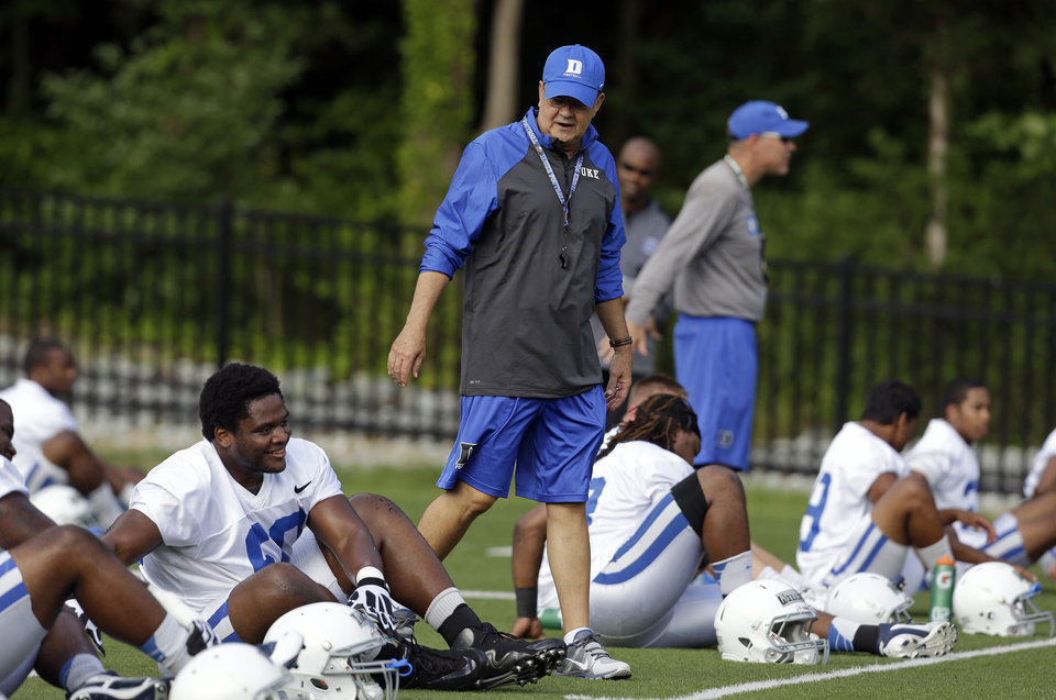 Photo - FILE - In this Monday, Aug. 5, 2013, file photo, Duke coach David Cutcliffe chats with players as they stretch during an NCAA college football practice in Durham, N.C. A growing number of college coaches are watching the social media behavior of student athletes, including Cutcliffe. (AP Photo/Gerry Broome, File)