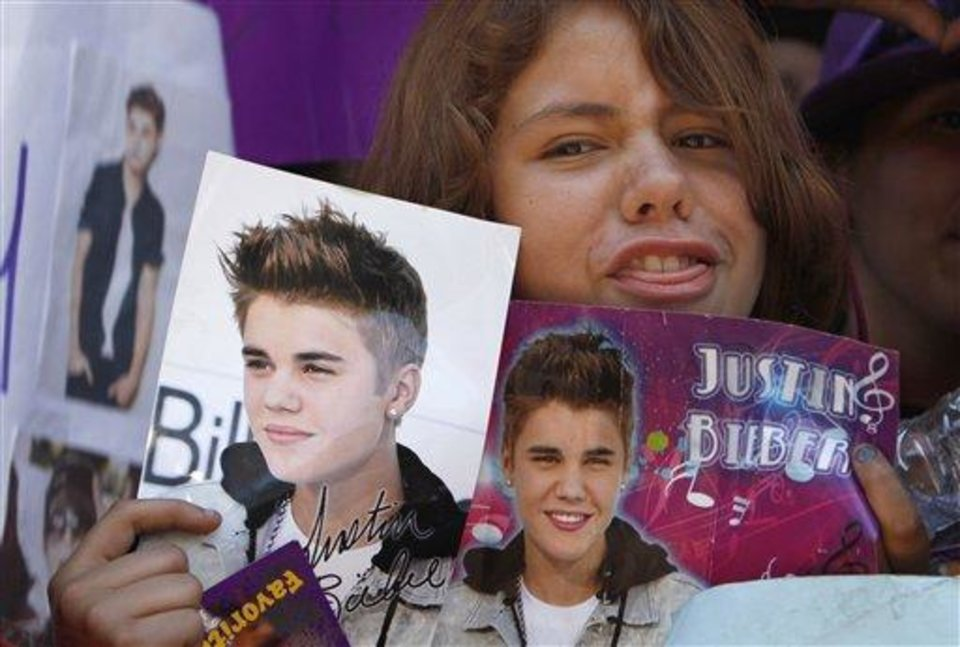 Photo - A fan holds images of pop starJustin Bieber in Mexico City's main historic plaza, the Zocalo, Sunday, June 10, 2012. The Beliebers have arrived in the chaotic streets of Mexico City, adolescents in purple and white and braving two nights on roach-infested sidewalks for a chance to be closest to the stage when teenage superstar Justin Bieber puts on a free concert Monday evening on the capital's vast central plaza. (AP Photo/Marco Ugarte)